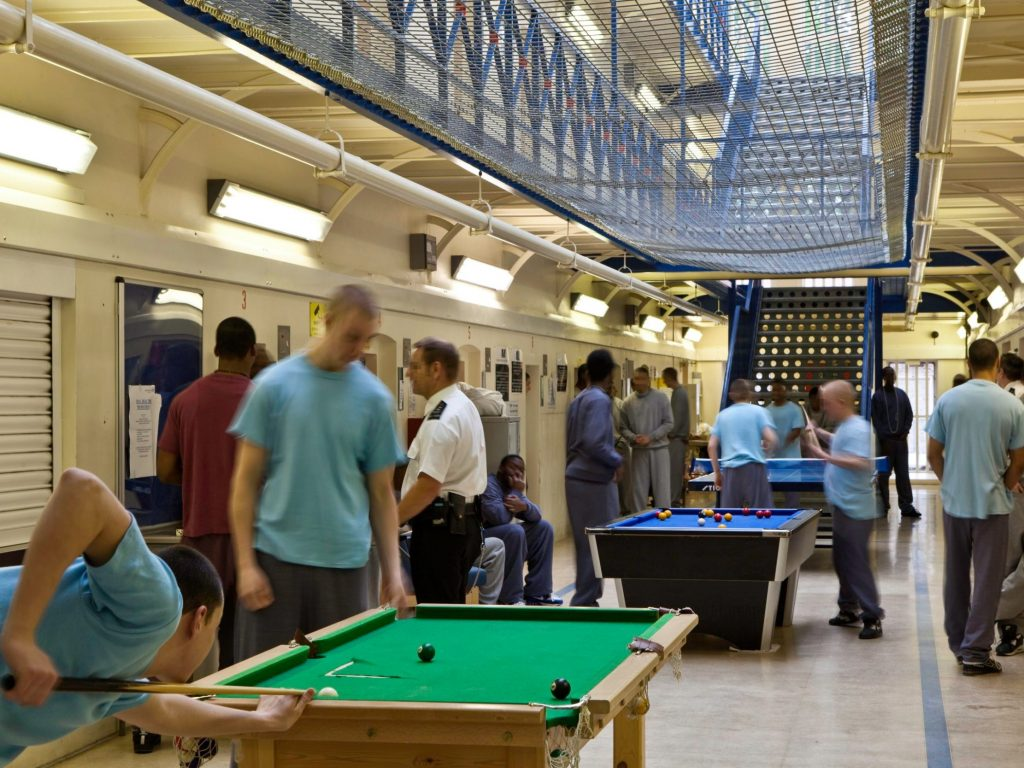 Young men playing pool in a young offenders institution