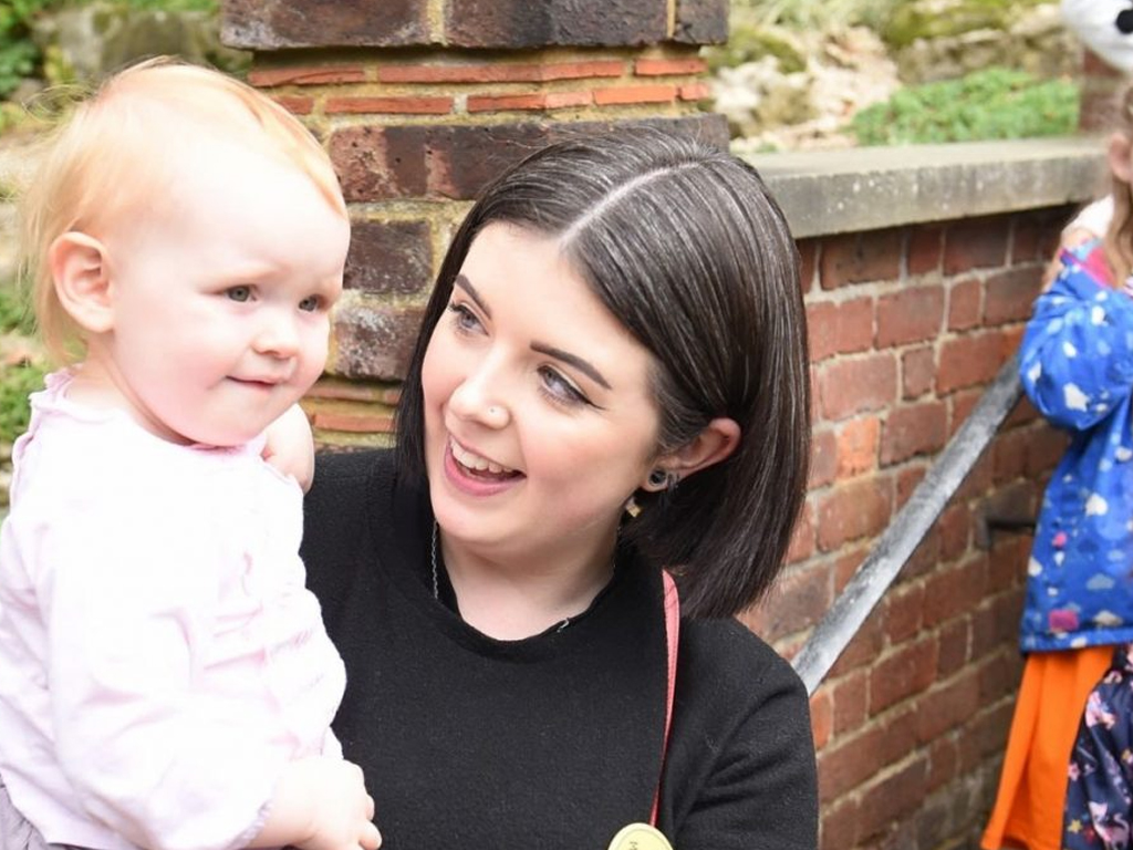 Woman smiling holding a baby